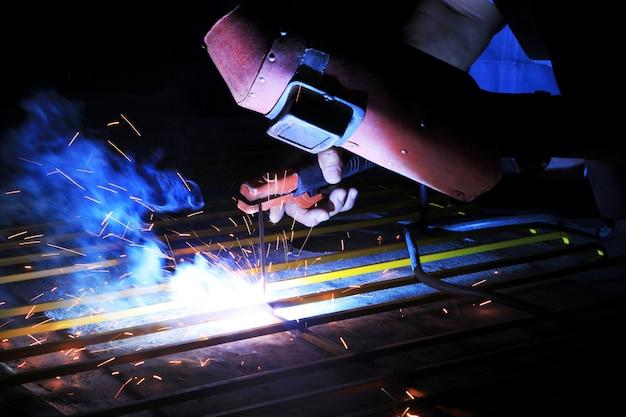 Schweißende stahlkonstruktion des industriearbeiters in der fabrik, schweißensbadekurort