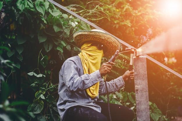 Schweißens-eisenstücke der arbeitskraft des jungen mannes bei der arbeit mit schutzbrillen