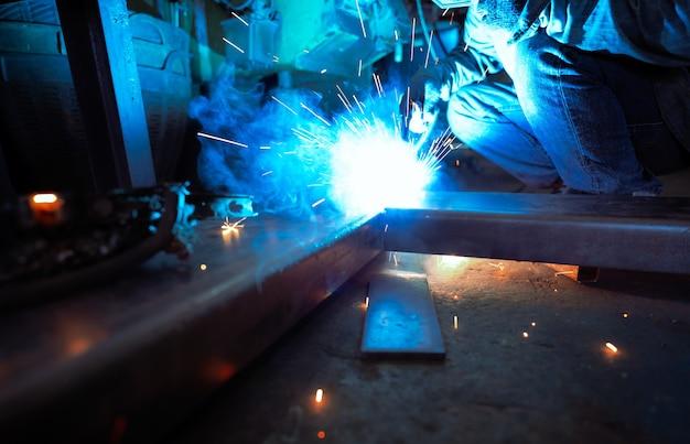 Schweißer, der metall mit argon-lichtbogenschweißgerät schweißt und schweißfunken hat. ein mann trägt schutzhandschuhe. sicherheit am industriearbeitsplatz. schweißer arbeitet mit sicherheit. arbeiter in einer fabrik der stahlindustrie.