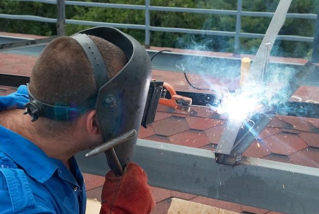 Schweißer in der fabrik arbeitet mit metallkonstruktion