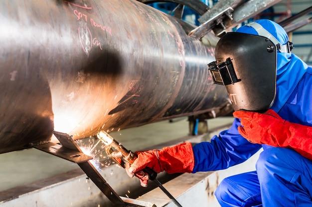 Schweißer in der fabrik, die metallrohre schweißt