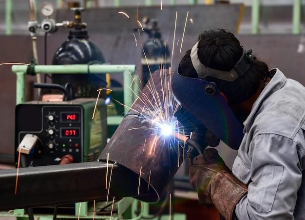 Schweißer in der fabrik mit schutzausrüstungsschweißrohr