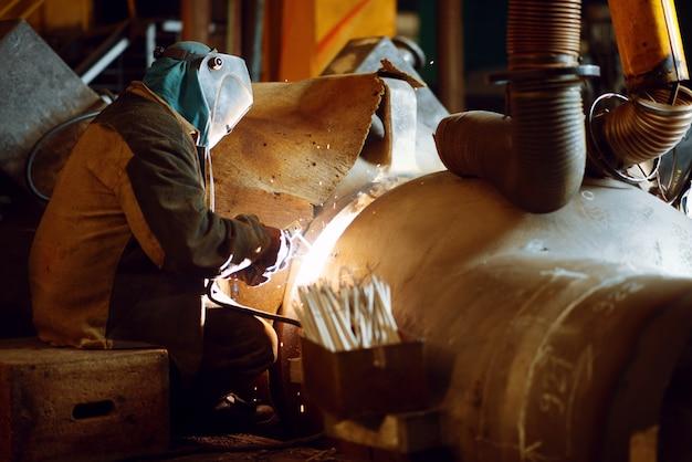 Schweißer in maske arbeitet mit metallkonstruktion