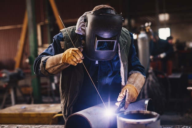 Schweißer in schutzkleidung und maske schweißen metallrohr auf dem industrietisch, während funken fliegen.
