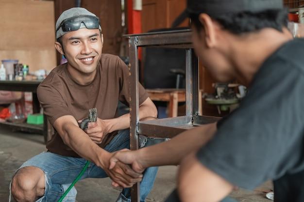 Schweißer und kunde geben sich in der werkstatt der schweißwerkstatt die hand