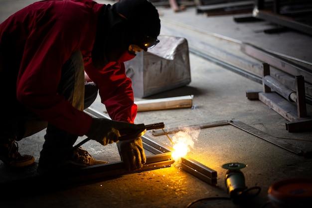 Schweißer verwendet schleifstein auf stahl in der fabrik mit funken, schweißprozess in der industriewerkstatt, hände mit instrument im rahmen.