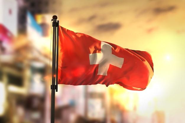 Schweiz flagge gegen stadt verschwommen hintergrund bei sonnenaufgang hintergrundbeleuchtung