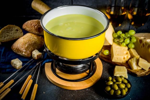 Schweizer feinschmeckerfondue im traditionellen fonduetopf mit gabeln, verschiedenen käsesorten, oliven, brot und trauben