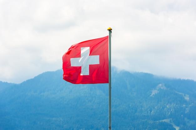 Schweizer flagge gegen alpenberge. horizontale aufnahme