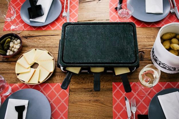 Schweizer traditionelles gericht namens raclette mit dampfenden kartoffeln, geschmolzenem käse und gurken, die zu weihnachten und im winter gegessen werden