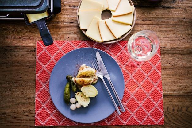 Schweizer traditionelles gericht namens raclette mit dampfenden kartoffeln, geschmolzenem käse und gurken