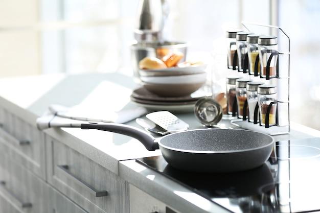 Schwenken sie auf einem modernen elektroherd in der küche neben dem fenster