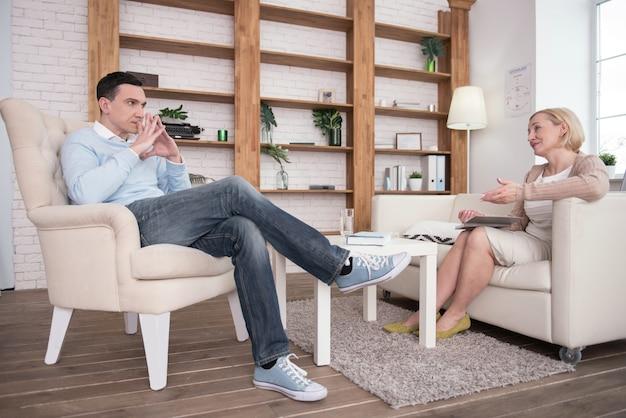 Schwer zu starten. aufmerksamer, fokussierter mann, der während der therapie sitzt, während er dem psychologen zuhört