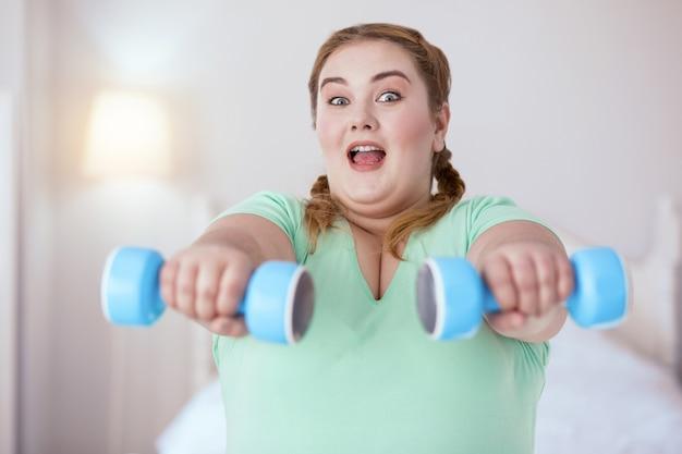 Schwere gewichte. überraschte junge frau, die hanteln während der übungen hält