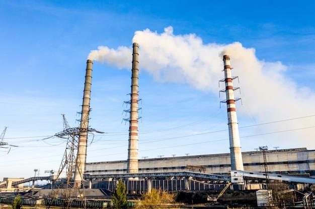 Schwere industriekohle trieb elektrizitätswerk mit rohren und rauche in schwarzweiss an