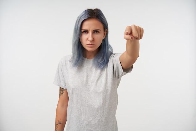 Schwere junge blauäugige tätowierte frau mit natürlichem make-up runzelte die stirn, während sie mit dem zeigefinger zeigte, isoliert auf weiß