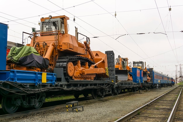 Schwere orangefarbene bulldozer stehen auf dem flachwagen des zuges für unfallbergungsarbeiten