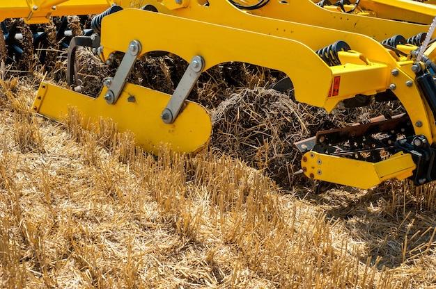 Schwere scheibenegge bei der arbeit, zum pflügen des landes landmaschinen für die bodenbearbeitung auf dem feld.