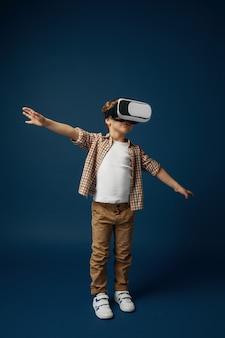 Schwerelos am himmel. kleiner junge oder kind in jeans und hemd mit virtual-reality-headset-brille lokalisiert auf blauem studiohintergrund. konzept der spitzentechnologie, videospiele, innovation.