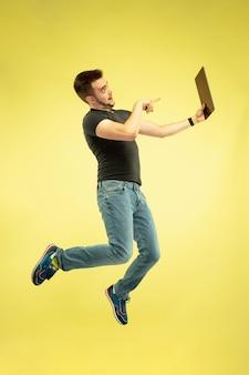 Schwerelos. porträt des glücklichen springenden mannes in voller länge mit gadgets lokalisiert auf gelbem hintergrund