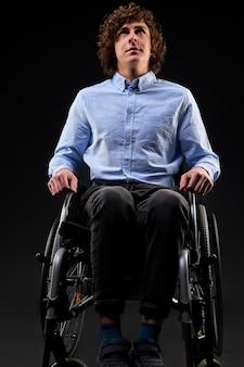 Schwerer kranker invalide kann nicht gehen, sitzt alleine im rollstuhl, fühlt sich einsam und unglücklich, hofft auf genesung. porträt