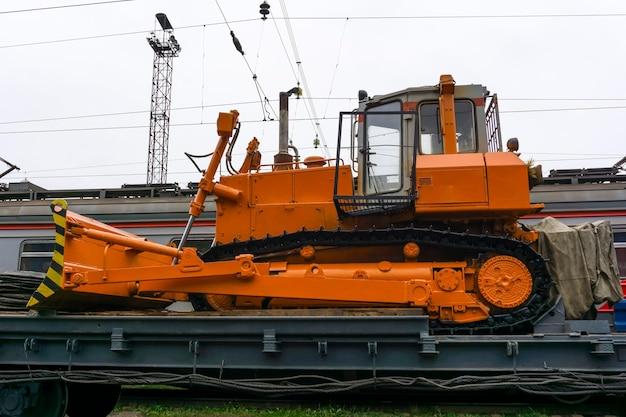 Schwerer orangefarbener bulldozer steht auf dem flachwagen des zuges für unfallbergungsarbeiten