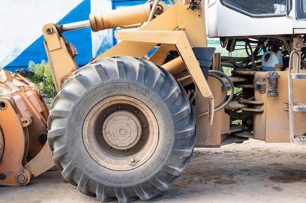 Schwerer radlader mit einer schaufel auf einer baustelle. ausrüstung für erdarbeiten, transport und verladung von schüttgütern - erde, sand, schotter.
