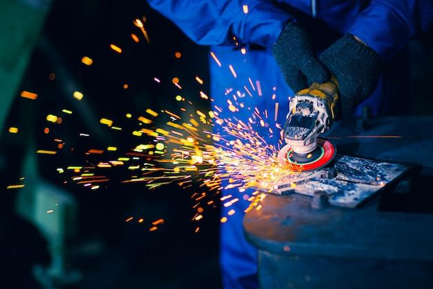 Schwerer stahlarbeiter der nahaufnahme unter verwendung der elektrischen radschleifscheibe, die metallplatte am arbeitsplatz schneidet