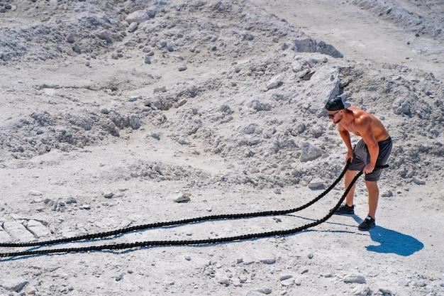 Schweres training in einem steinbruch. intensives training mit seilen in weißen bergen. starker attraktiver bodybuilder. lebensstil. weiße landschaft.