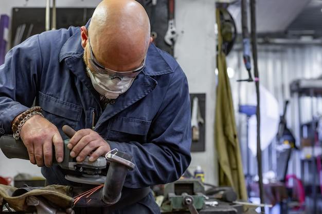 Schwerindustriearbeiter, der stahl mit winkelschleifer am autoservice schneidet