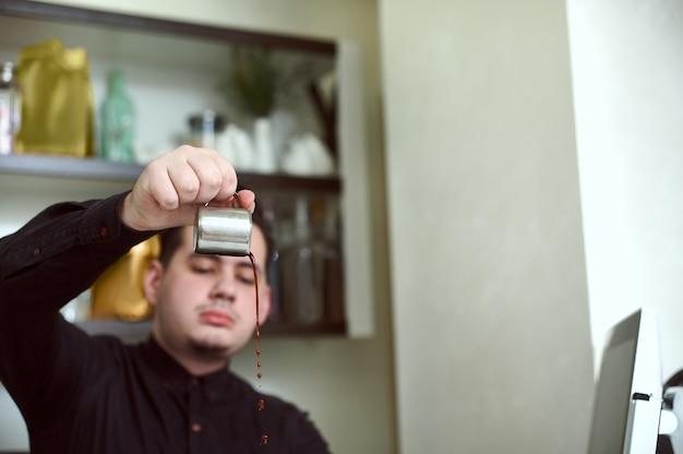 Schwerpunkt auf kaffeetröpfchen, die in den händen junger baristas aus dem behälter strömen