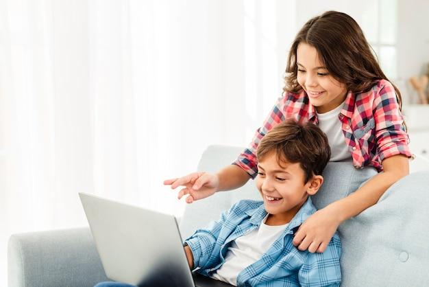 Schwester, die bruder etwas auf laptop zeigt