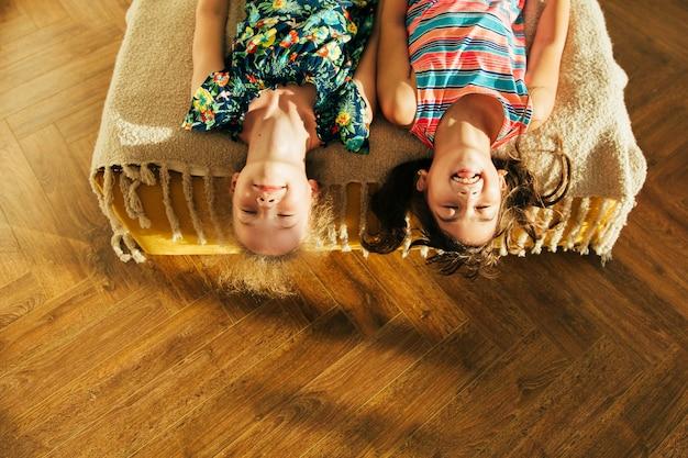Schwester, die spaß im schlechten hat und momente der liebe teilt. kleine mädchen, die spaß zusammen im bett haben. kleine mädchen, die zu hause auf bett spielen.