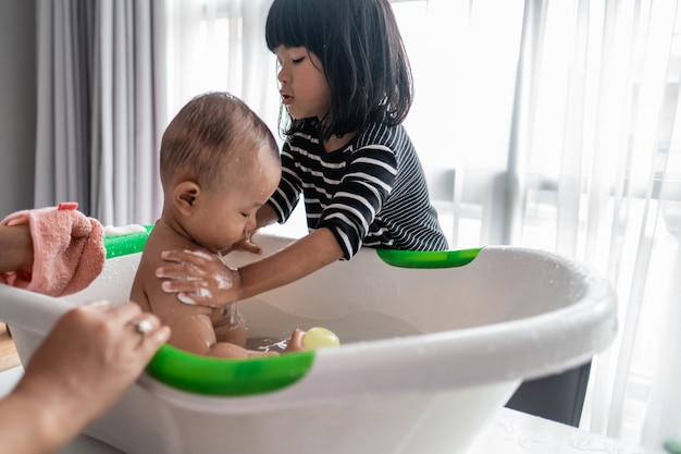 Schwester hilft ihrem kleinen bruder beim baden