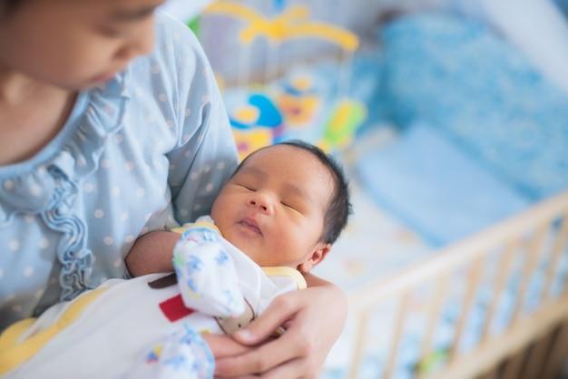 Schwester holt asiatischen neugeborenen bruder zum schlafen