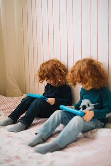 Schwester mit zwei zwillingen, die auf dem bett betrachtet tragbare digitale tabletten sitzt