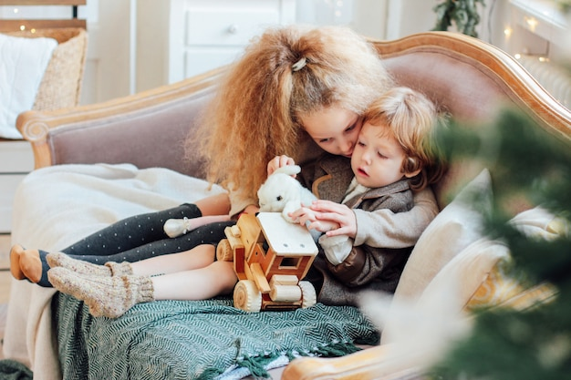Schwester umarmt kleinen bruder auf der couch, gemütlicher wintertag