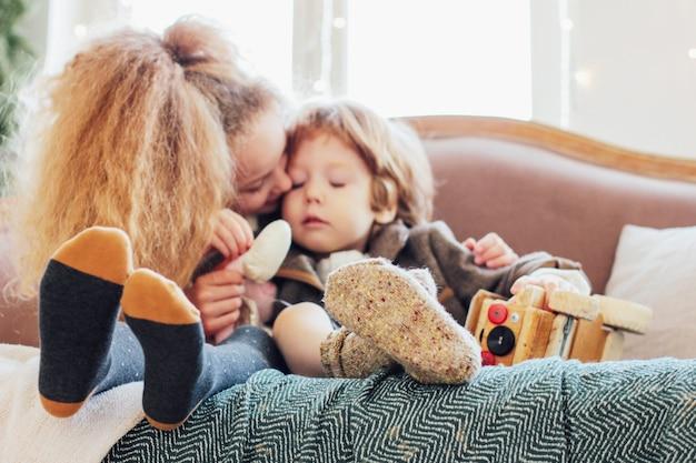 Schwester umarmt kleinen bruder auf der couch, konzentriert sich auf die beine in warmen s
