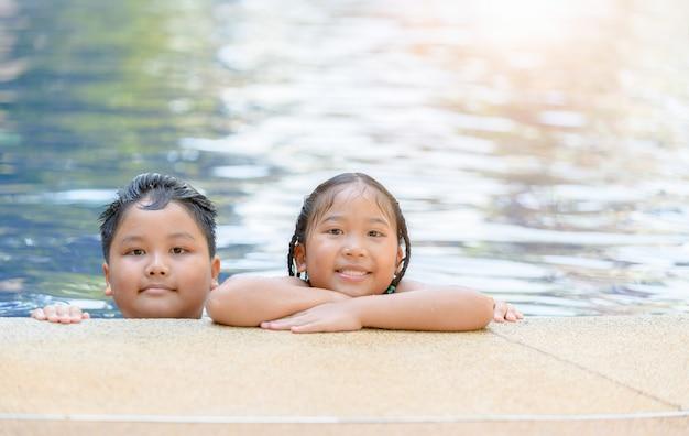 Schwester und bruder, die am swimmingpool spielen,