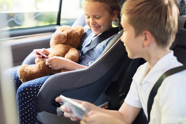 Schwester und bruder, die mit digitalen geräten im auto spielen