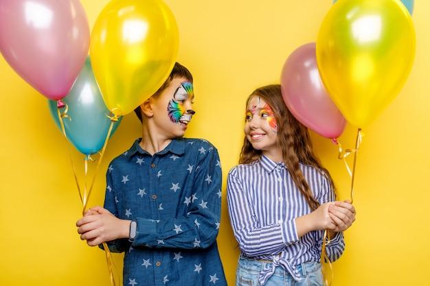 Schwester und bruder mit faceart halten gegenwärtige ballons isoliert auf gelber wand