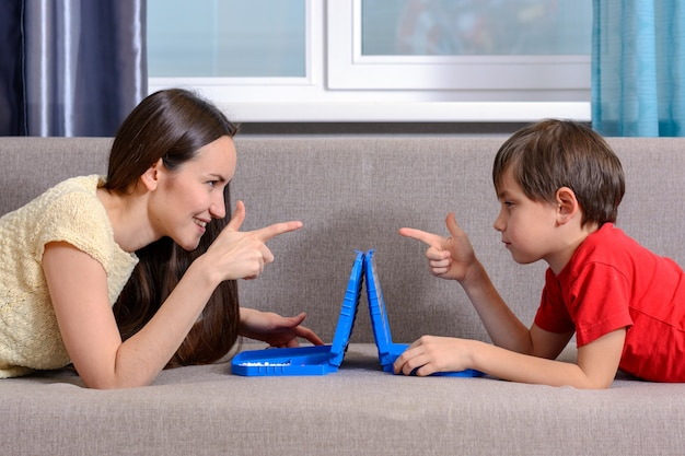 Schwester und jüngerer bruder spielen ein schlachtschiff, liegen auf der couch im raum und schauen sich in die augen.