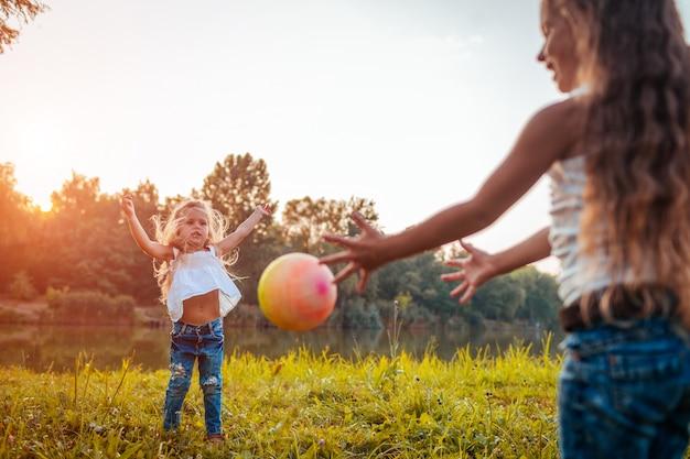 Schwestern der kleinen mädchen, die mit ball im sommerpark spielen. kinder haben spaß im freien.