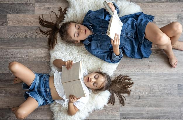 Schwestern der kleinen mädchen lesen bücher, die auf dem boden liegen, draufsicht.