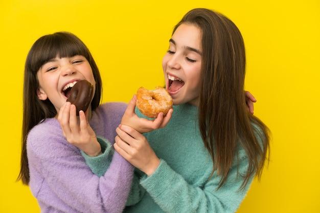 Schwestern, die einen donut über isoliertem hintergrund halten
