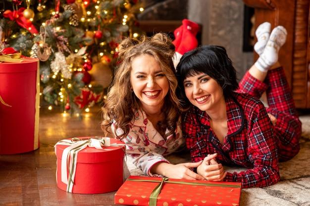 Schwestern, die nahe geschmücktem rotem weihnachtsbaum liegen. sie lachen und feiern weihnachten.