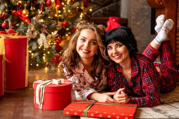 Schwestern, die nahe geschmücktem rotem weihnachtsbaum liegen. sie lächeln und feiern weihnachten.