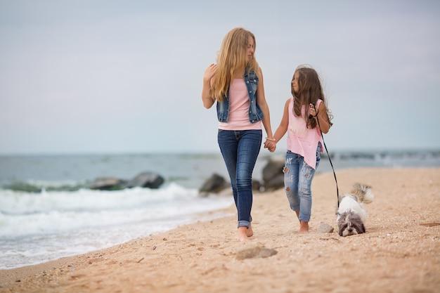 Schwestern gehen mit einem hund in rosa t-shirts und blue jeans am meer spazieren
