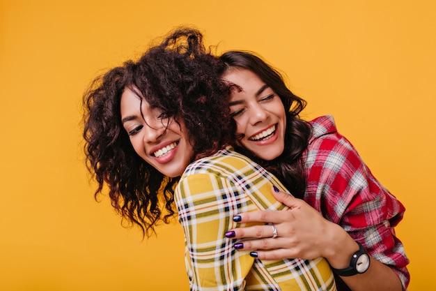 Schwestern haben sich lange nicht gesehen und gebräuntes mädchen beeilte sich, mulatten im gelben oberteil zu umarmen.
