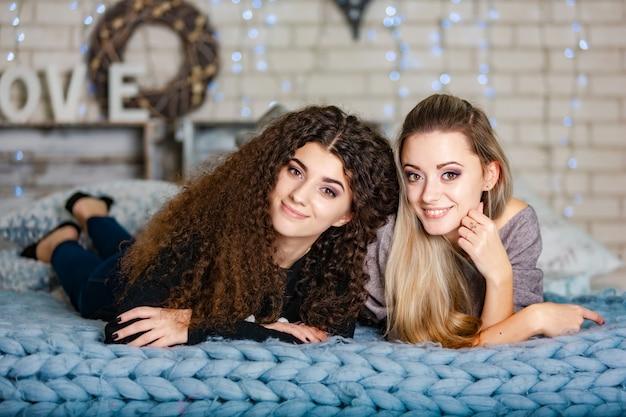 Schwestern in warmen pullovern mit mini-neujahrsmützen lagen auf einem plaid.